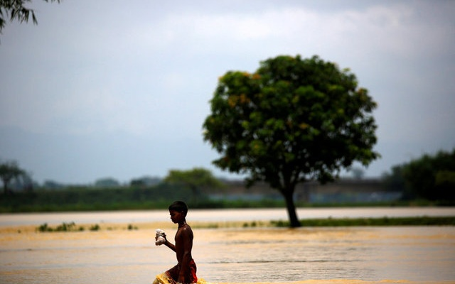A boy walks along the flooded area in Saptari District, Nepal August 14, 2017. REUTERS/Navesh Chitrakar TPX IMAGES OF THE DAY