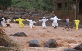 People wearing protective suits hold hands as they cross a river after a mudslide in the mountain town of Regent, Sierra Leone August 15, 2017 in this still image taken from a video. Reuters