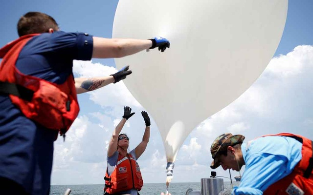 College of Charleston professor Dr Cassandra Runyon (Centre) releases a balloon during a test launch for the Space Grant Ballooning Project in preparations for Monday's solar eclipse on board a US Coast Guard response boat at sea near Charleston, South Carolina, US Aug 17, 2017. Location coordinates for this image are 32º41' 975
