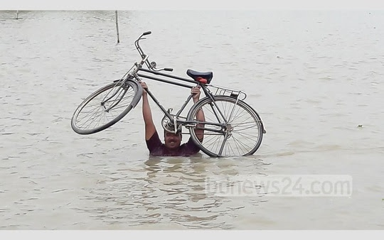 ​This picture tells the flood situation of Sadar Upazila in Naogaon where Atrai river burst its bank and inundated the vast area. ​The photo of the man with his precious bicycle was taken on Friday.