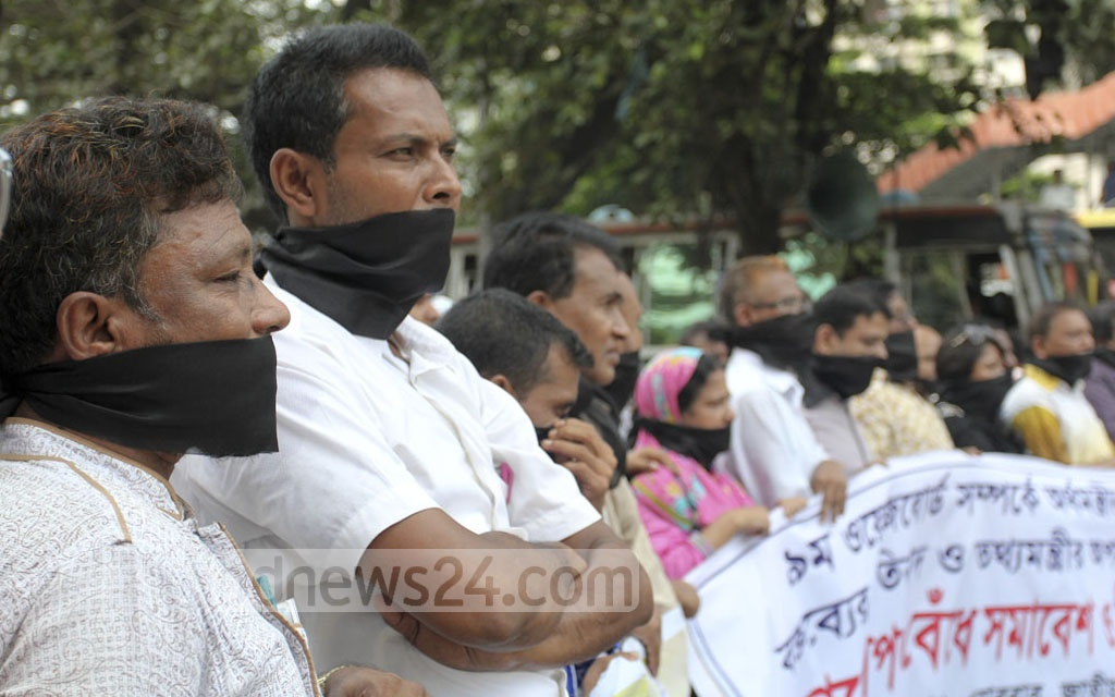 Journalists covered parts of their face with black clothes and blocked the city thoroughfare in front of the National Press Club in Dhaka on Sunday to protest the 'unseemly comment' of the finance minister about 9th Wage Board for media professionals. They also demanded his removal from the Cabinet.