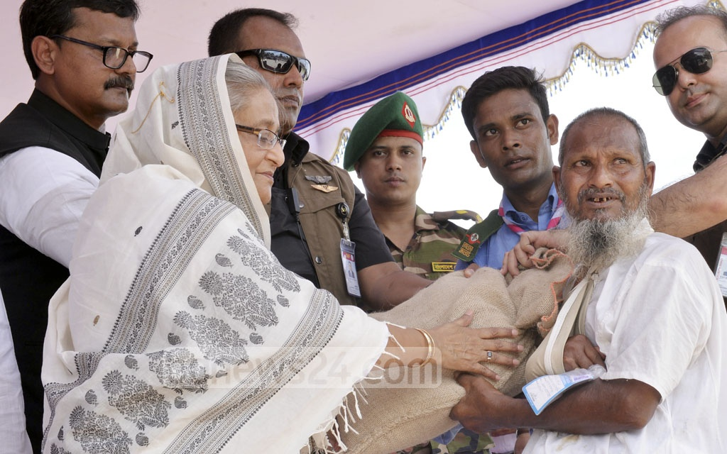 Prime Minister Sheikh Hasina gives food aid to victims of Dinajpur's flood on Sunday. Photo: PID