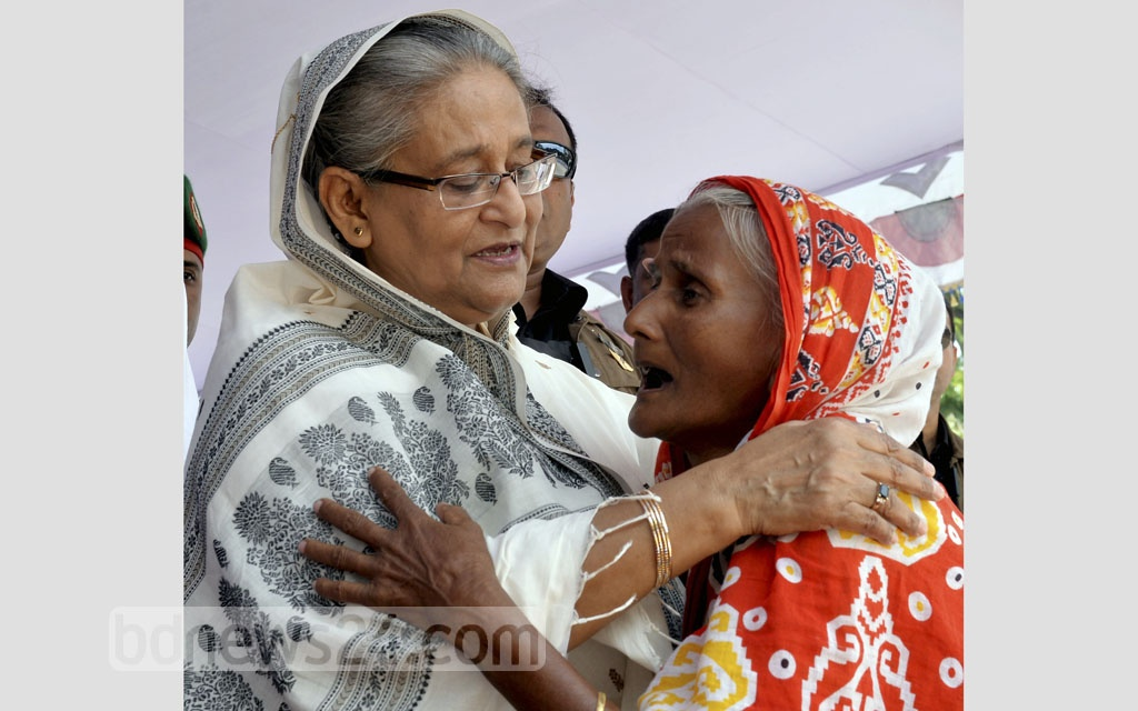 Prime Minister Sheikh Hasina comforts a woman during a programme to distribute relief items among flood victims at Dinajpur on Sunday. Photo: PID