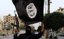 A member loyal to the Islamic State in Iraq and the Levant (ISIL) waves an ISIL flag in Raqqa June 29, 2014. Photo: Reuters