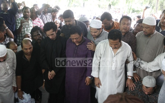 Razzak's sons Bappi, Bapparaj and Samrat look at their father one last time before his burial. Photo: tanvir ahammed
