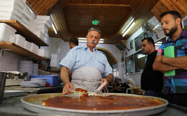 A Palestinian man serves knafa, a sweet semolina and cheese pastry, at al Aqsa sweet shop in the historic covered market of Nablus in the West Bank August 10, 2017. Reuters