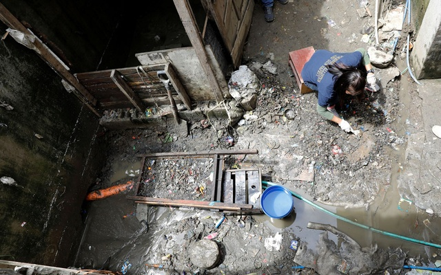 A member of Philippine National Bureau of Investigation gathers evidence at the site where Kian delos Santos, a 17-year-old student was killed during anti-drug operations in Caloocan, Metro Manila, Philippines Aug 22, 2017. Reuters