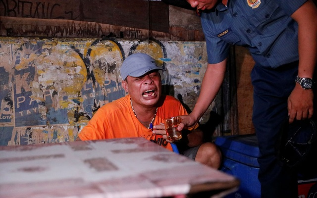 File photo - A police officer gives a glass of water to a man as he comforts him after his brother was shot, who police said was killed in a spate of drug related violence overnight in Manila, Philippines Aug 16, 2017. Reuters
