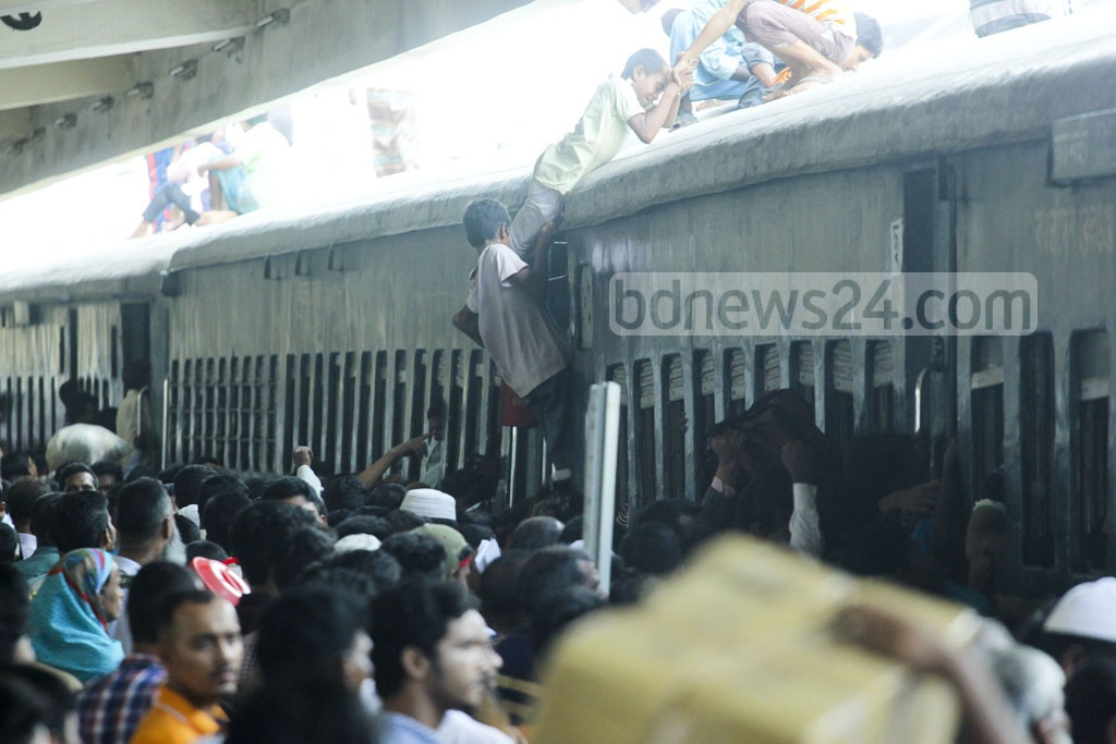 People try to desperately secure spots on the roof of trains as they head for their hometowns before Eid-Ul-Azha. The photo was taken at Dhaka's Kamalapur Railway Station on Monday. Photo: abdul mannan