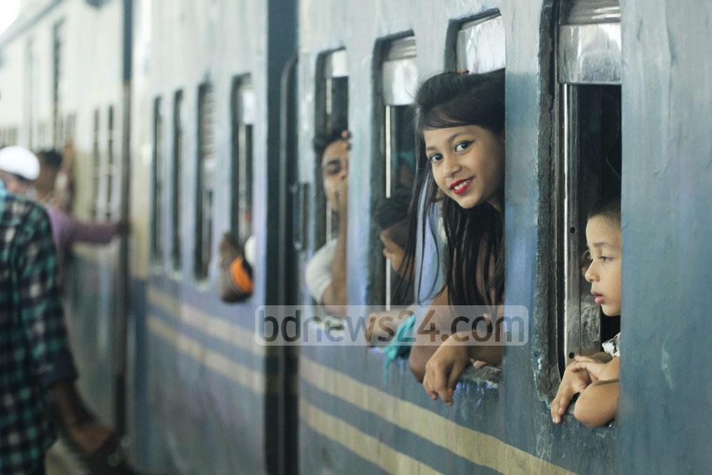 A girl smiles as she looks out a train window at Dhaka's Kamalapur Railway Station. With just few days before Eid-ul-Azha, the joy of travelling on holiday was visible on young faces. Photo: abdul mannan