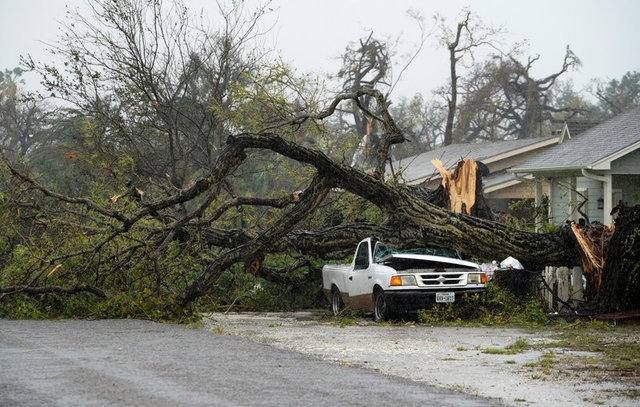 A car is crushed by a huge tree after Hurricane Harvey struck in Rockport, Texas, August 26, 2017. reuters