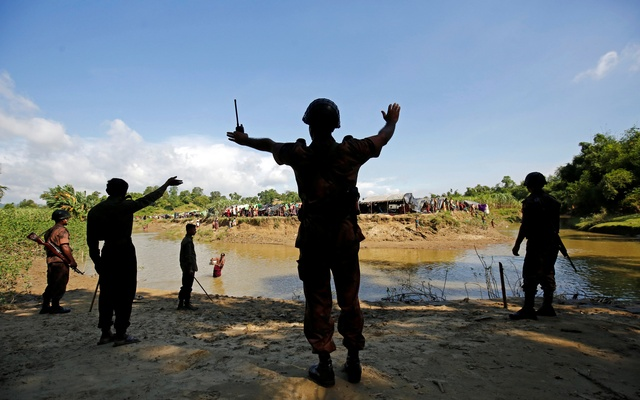 Members of Border Guard Bangladesh (BGB) command to the Rohingya people not to cross the canal, who take shelter in No Man's Land between Bangladesh-Myanmar border, in Cox's Bazar, Bangladesh, August 27, 2017. Reuters
