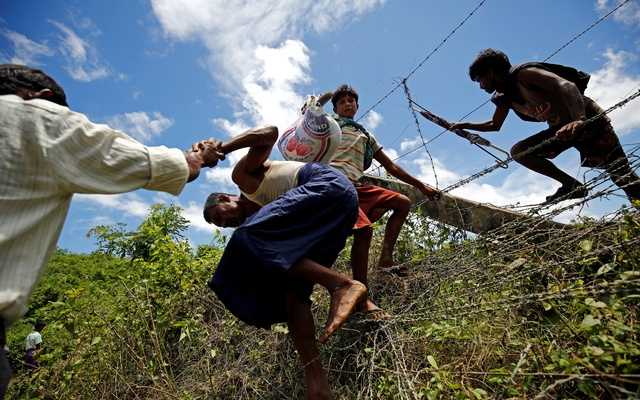 Rohingya people cross the border fence to enter inside Bangladesh border, in Cox's Bazar, Bangladesh, August 27, 2017. Reuters
