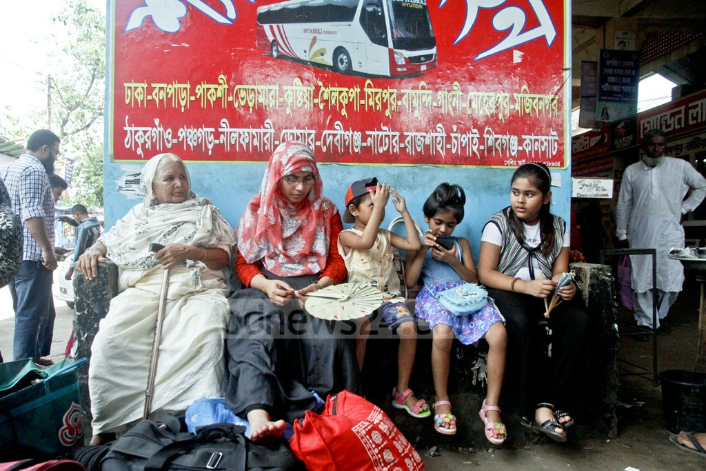 Family members wait at the Gabtoli Bus Terminal where huge crowds of home-bound people had descended on Tuesday.