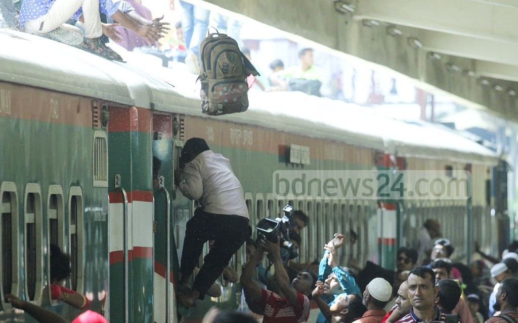 People desperately try to get space on the roof of trains as they head for their hometowns and villages to spend Eid-Ul-Azha holidays with loved ones. The photo was taken at Dhaka's Kamalapur Railway Station on Tuesday. Photo: abdul mannan