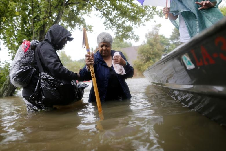Andrew Mitchell helps his neighbor Beverly Johnson onto a rescue boat in Beaumont Place, Houston, Texas. Reuters