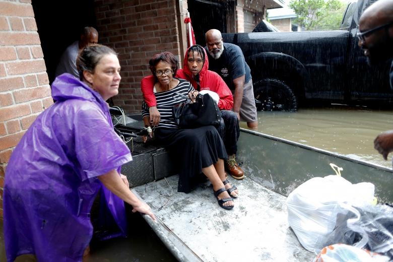 The Hawkins family is rescued from the flood waters in Beaumont Place, Houston, Texas. Reuters