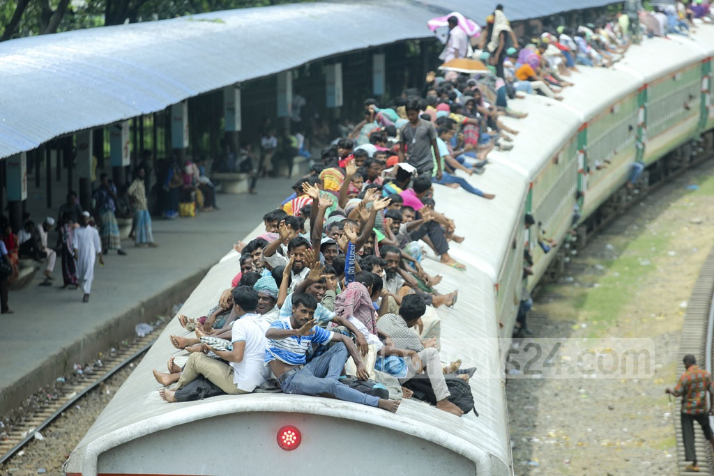 After desperate bids to board their train, holidaymakers wave at the camera as they leave Dhaka's Airport Railway Station on Wednesday. Photo: abdul mannan