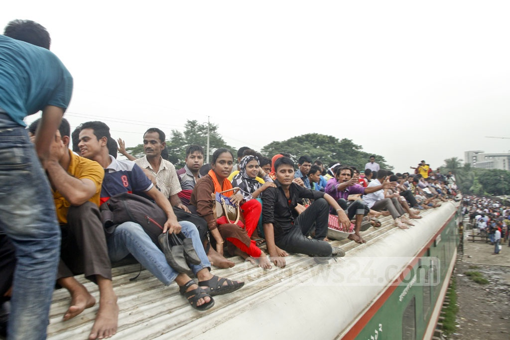 Homebound people risk their lives by travelling on the roof of a train to celebrate Eid-ul-Azha with their loved ones. The photo was taken at Dhaka Airport Railway Station on Thursday. Photo: tanvir ahammed