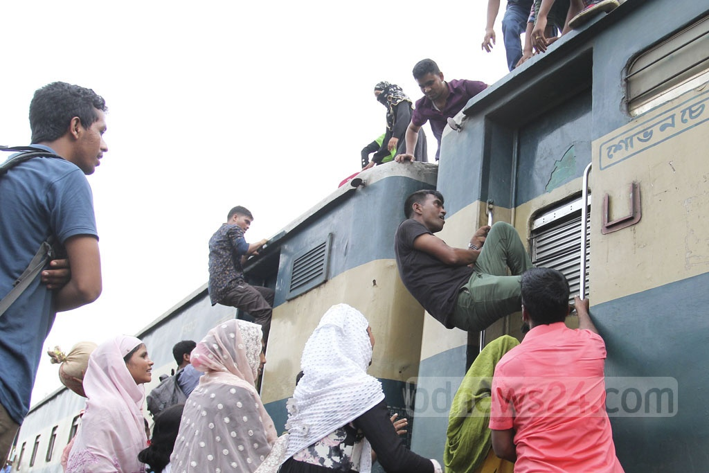 People trying to ride the roof of a train at Dhaka Airport Railway Station on Thursday in desperate efforts to celebrate Eid-ul-Azha with their families back home as the compartments are already crammed with homebound holidaymakers. Photo: asif mahmud ove