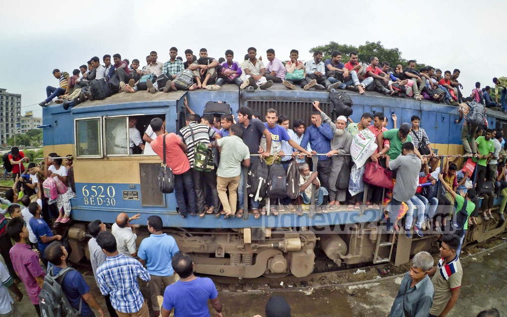 Homebound people risk their lives by travelling on the roof of a train to celebrate Eid-ul-Azha with their loved ones. The photo was taken at Dhaka Airport Railway Station on Thursday. Photo: asif mahmud ove