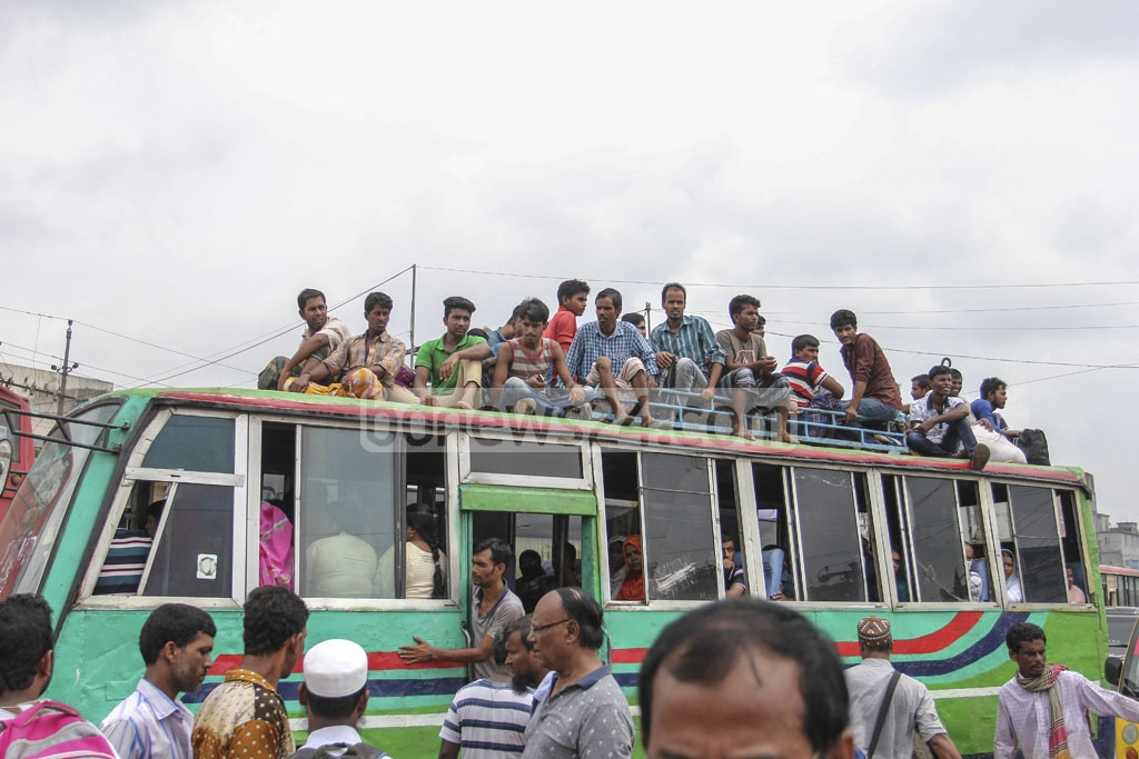 Many passengers risk their lives by travelling on bus rooftops to reach ancestral homes to celebrate Eid-ul-Azha with family and loved ones. The photo is taken at Gabtoli Bus Terminal in Dhaka on Friday. Photo: asif mahmud ove