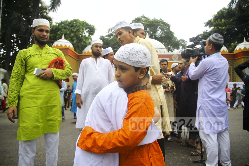 Children exchange greetings after the Eid congregation at National Eidgah Ground on Saturday.