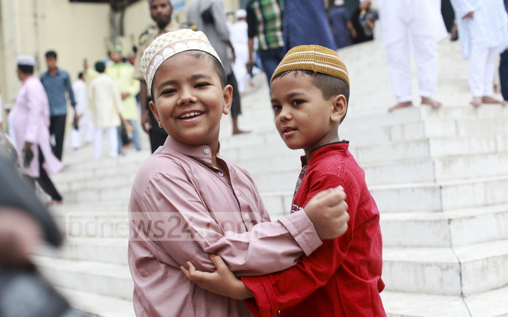 Children exchange greetings after the Eid congregation at Baitul Mukarram National Mosque on Saturday.