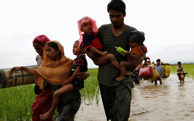 A group of Rohingya refugees carry their children as they wade across water after travelling over the Bangladesh-Myanmar border in Teknaf, Bangladesh, September 1, 2017. Reuters