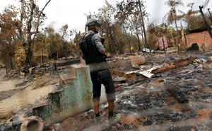 A police officer stands in a house that was burnt down during the days of violence in Maungdaw, Myanmar August 30, 2017. Picture taken August 30, 2017. Reuters