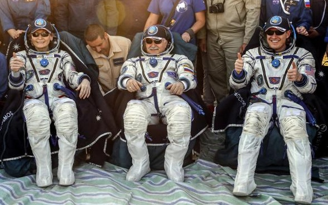 Members of the International Space Station (ISS) crew Peggy Annette Whitson of the U.S. (L), Fyodor Yurchikhin of Russia (C), and Jack Fischer of the U.S. rest shortly after the landing of the Soyuz MS-04 capsule in a remote area outside the town of Dzhezkazgan (Zhezkazgan), Kazakhstan September 3, 2017. Reuters