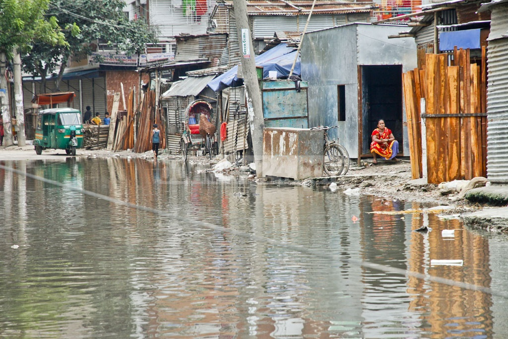 Life goes on beside the stinky stagnant water that flooded the road adjacent to Shia Masjid in Mohammadpur.Residents said they had been suffering from the water stagnation for over a month. The photo is taken on Tuesday.