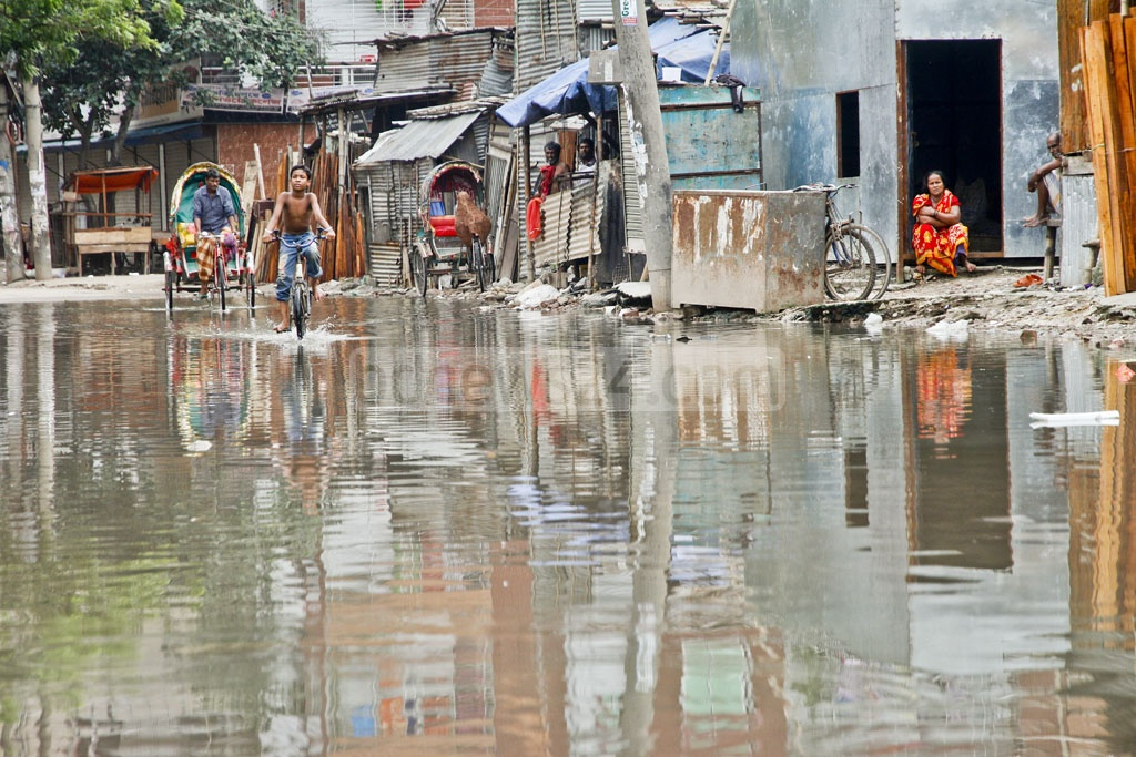 Life goes on beside the stinky stagnant water that flooded the road adjacent to Shia Masjid in Mohammadpur. Residents said they had been suffering from the water stagnation for over a month. The photo is taken on Tuesday.