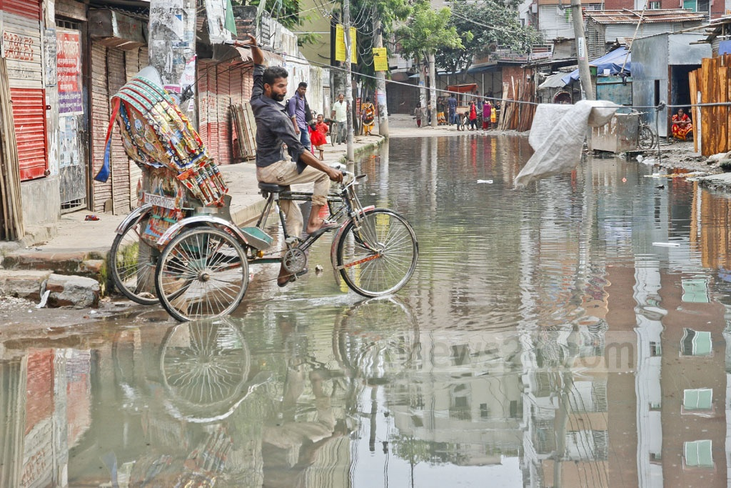 Stagnant water flooded the road adjacent to Shia Masjid in Mohammadpur even when there was no rain. Residents put up some barriers to alert the commuters so that they can avoid accidents.The photo is taken on Tuesday.