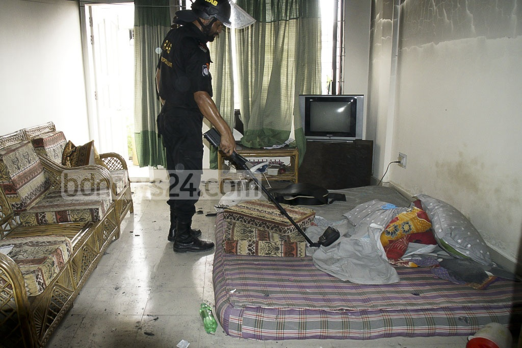 A member of the Rapid Action Battalion searches a flat on Mirpur's Mazar Road where a militant suspect set off a series of explosions.