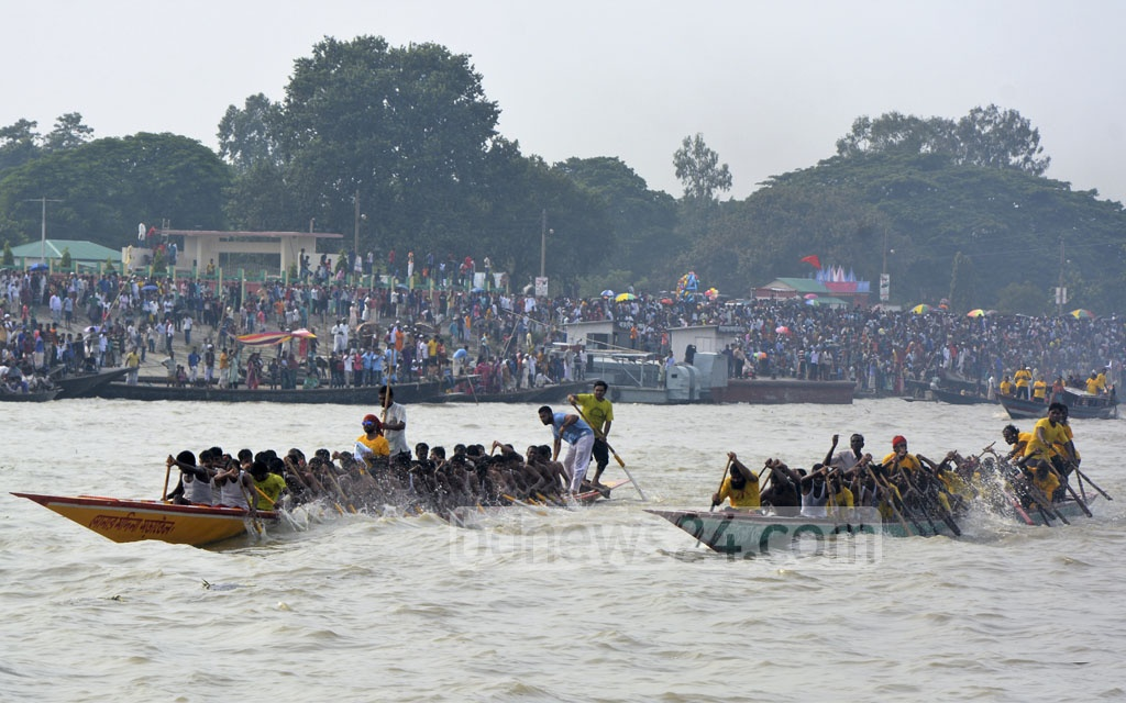 Participants row boats in a race organised by Sirajganj district administration and sports association in the river Jamuna on Thursday.