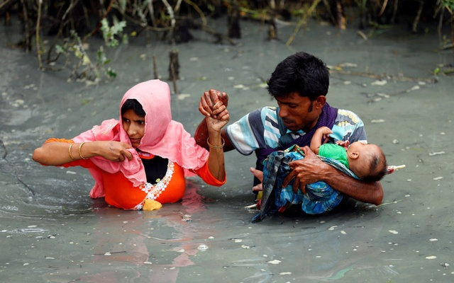 Rohingya refugees carry their child as they walk through water after crossing border by boat through the Naf River in Teknaf, Bangladesh, September 7, 2017. Reuters