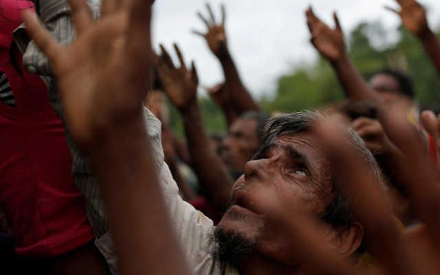 Rohingya refugees stretch their hands to receive food distributed by local organizations in Kutupalong, Bangladesh, September 9, 2017. Reuters