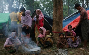 Rohingya refugees go about their day outside their temporary shelters along a road in Kutupalong, Bangladesh, September 9, 2017. Reuters
