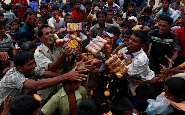 Rohingya refugees jostle to receive food distributed by local organizations in Kutupalong, Bangladesh, September 9, 2017. Reuters