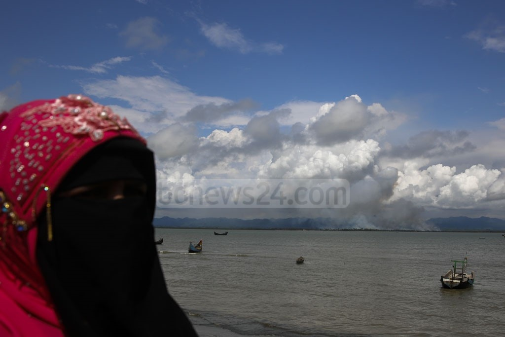 ​​​A Rohingya woman watches her ​house in Maungdaw burning in apparent horror from Shah Porir Dwip in Teknaf.​​ Photo: mostafigur rahman