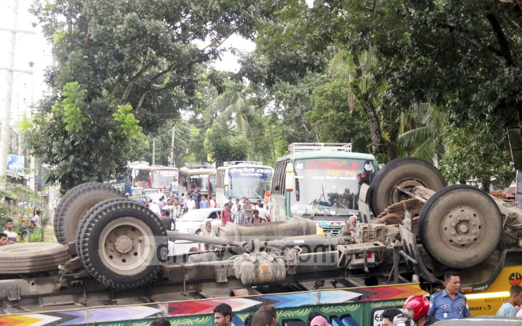 Hundreds of cars are stuck in traffic after a truck overturns and blocks both sides of the road in the Kakiar Bazar area of Srimangal on Monday.