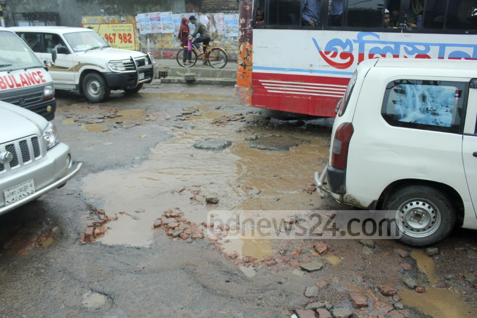 Sufferings due to potholes on streets apoear a never-ending problem of the residents of Dhaka. The photo is taken in Nabisco area of Tejgaon on Monday.