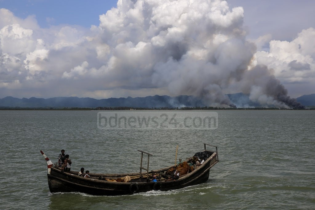 Smoke is seen on the Myanmar's side of border as Rohingyas fleeing the Maungdaw township Rakhine State with their cattle. Photo: mostafigur rahman