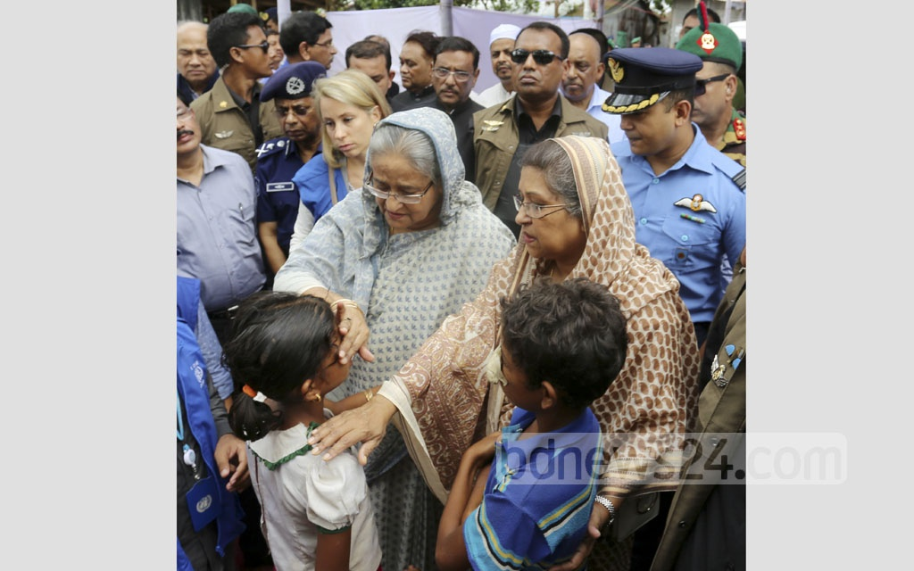 Prime Minister Sheikh Hasina, with her sister Sheikh Rehana and Rehana's daughter-in-law and IOM official Peppi Kiviniemi-Siddiq beside her, speaks to two wounded Rohingya children at the Kutupalong refugee camp in Cox's Bazar's Ukhia on Tuesday. Photo: habibur rahman