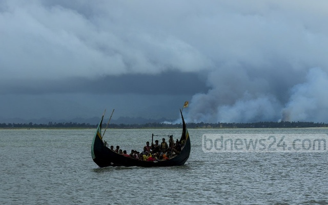 Representational Image: A boat carrying Rohingya refugees cross the Naf river to Shah Porir Dwip of Bangladesh as smoke is seen rising from burning homes on the other side in Myanmar's Rasidong on Sept 12, 2017. File Photo: mostafigur rahman