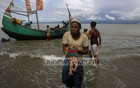 A Rohingya man carries an infant to the shore from a boat that arrived in Shah Porir Dwip of Bangladesh from Rasidong in Myanmar. Photo: mostafigur rahman