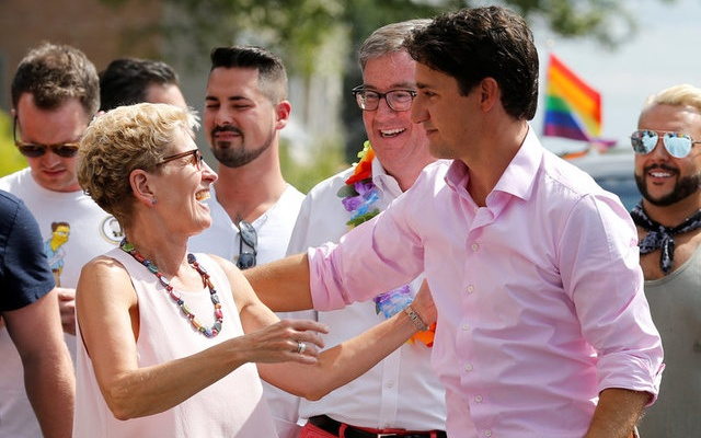 Canada's Prime Minister Justin Trudeau (R) embraces Ontario Premier Kathleen Wynne (L) as Ottawa Mayor Jim Watson (C) looks on during the Ottawa Pride Parade in Ottawa, Ontario, Canada, August 27, 2017. Reuters