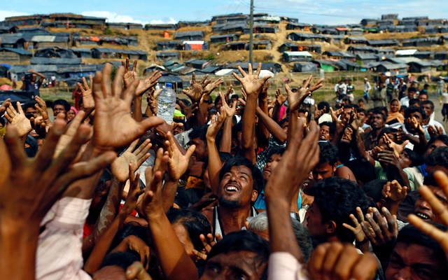 Rohingya refugees stretch their hands to receive aid distributed by local organisations at a makeshift refugee camp in Cox's Bazar on Sept 14. Reuters