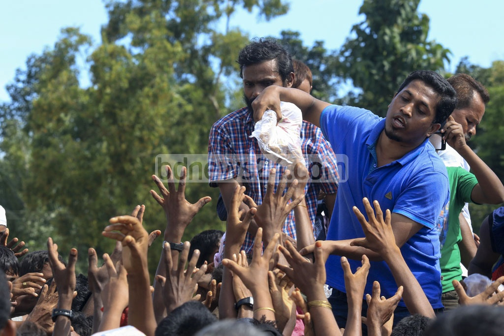 Rohingya refugees stretch their hands for relief materials at Palongkhali in Ukhia, Cox's Bazar on Saturday as aid workers throw clothes from a truck. Photo: muhammad mostafigur rahman